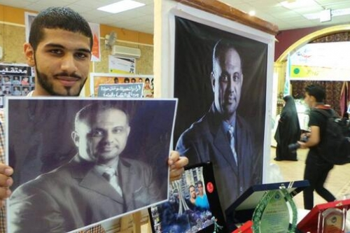 Jaffar holding photo of his imprisoned father